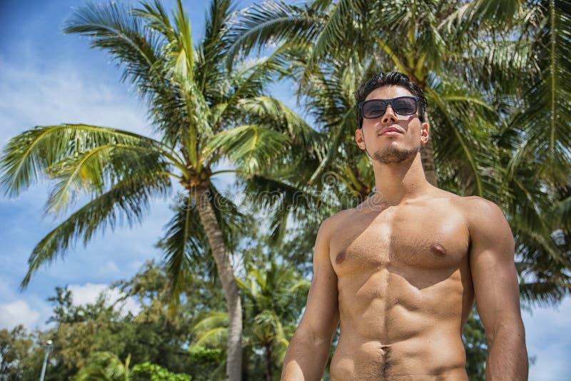 Uomo senza camicia bello che esamina macchina fotografica fotografia stock libera da diritti