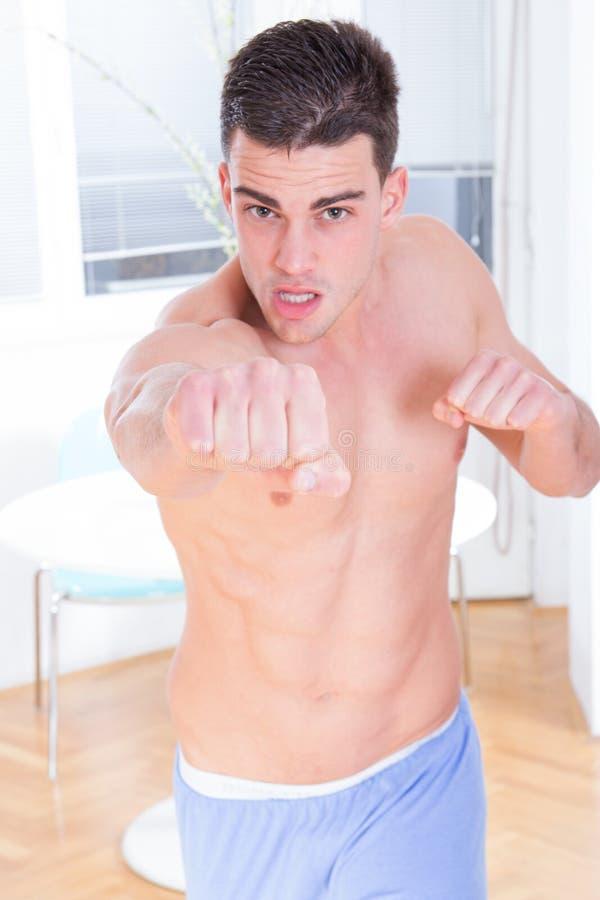 Uomo senza camicia che esercita lotta e perforazione a casa immagini stock libere da diritti
