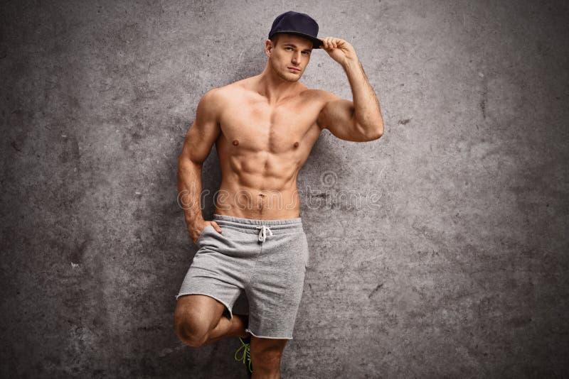 Uomo senza camicia che pende contro una parete grigia arrugginita immagini stock libere da diritti