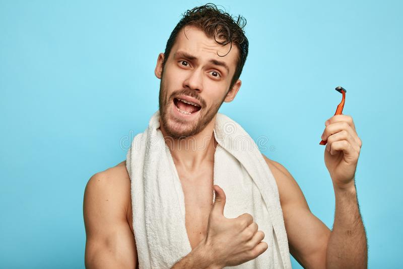 Uomo senza camicia emozionale che va collaudare di nuovo rasoio fotografia stock libera da diritti