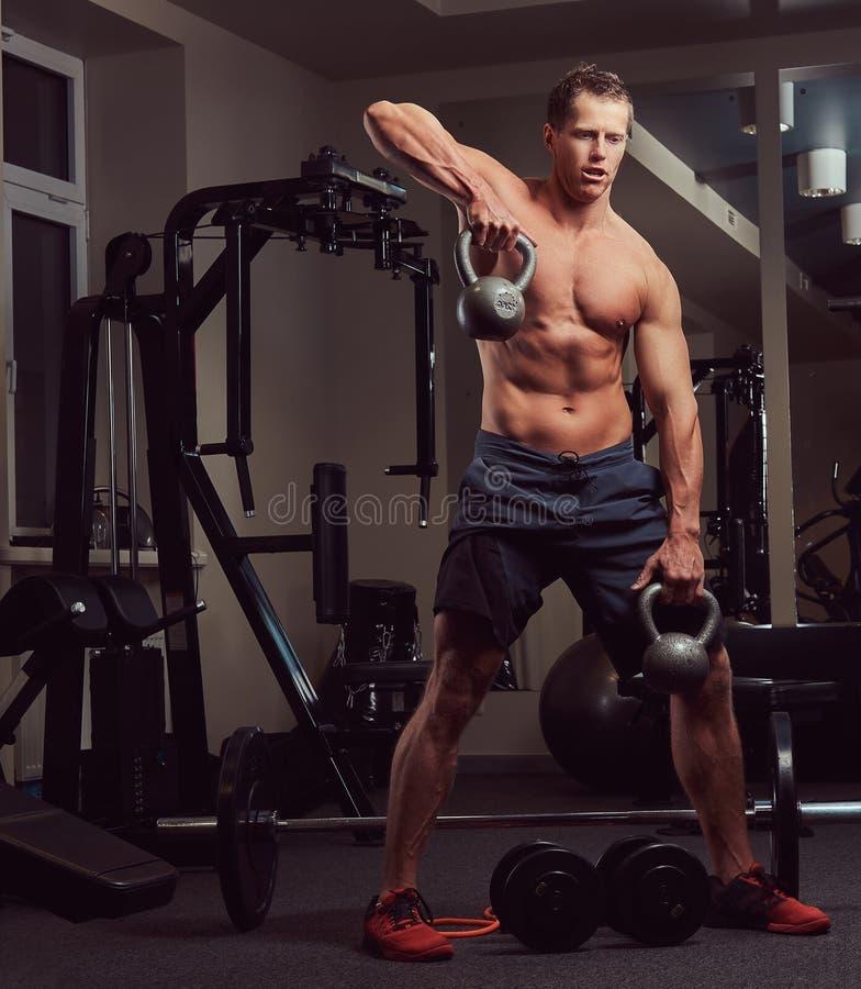 Uomo senza camicia muscolare bello del culturista che fa gli esercizi sui muscoli di deltoide con un kettlebell nella palestra immagini stock libere da diritti