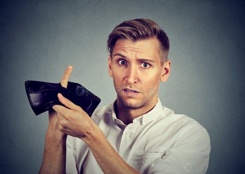 Uomo senza soldi che tengono portafoglio vuoto immagine stock
