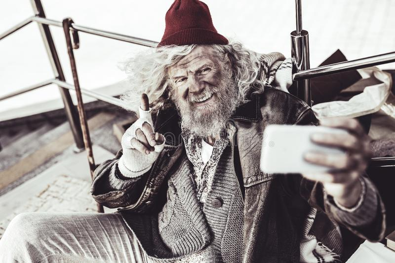 Uomo senza tetto anziano che gesticola mentre parlando sul video dal telefono fotografie stock libere da diritti