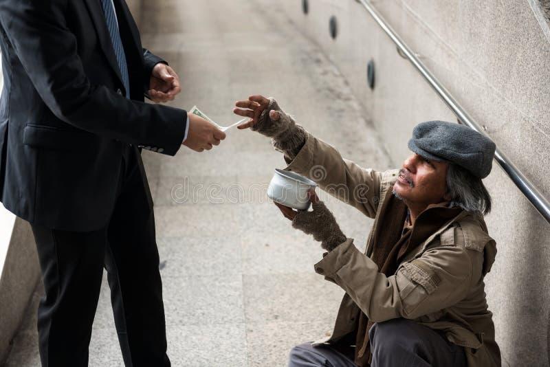 Uomo senza tetto anziano in città, concetto di aiuto fotografia stock