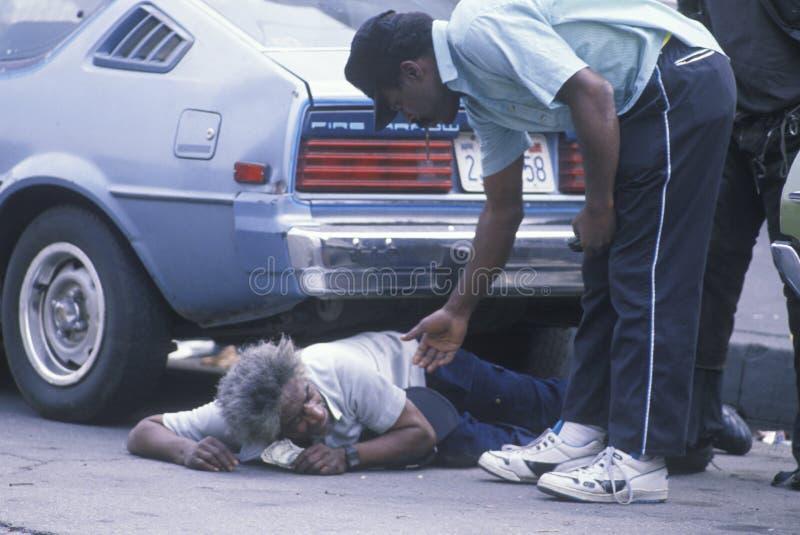 Uomo senza tetto caduto in via della città che ottiene aiuto, Los Angeles, California immagini stock