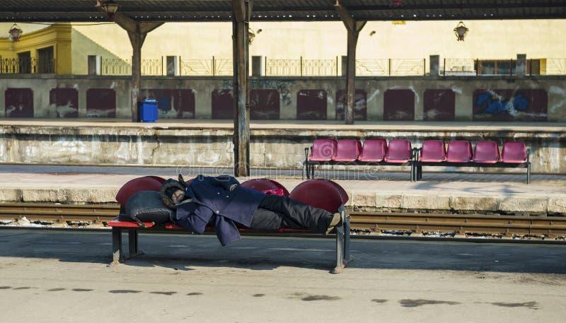 Uomo senza tetto che dorme nella stazione ferroviaria del nord di Bucarest fotografia stock
