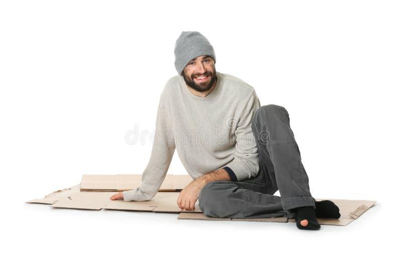 Uomo senza tetto che si siede sul cartone, fondo bianco fotografia stock libera da diritti