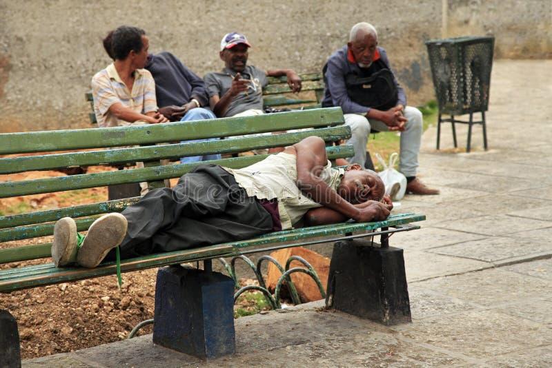 Uomo senza tetto che si trova su un banco a vecchia Avana, Cuba immagini stock libere da diritti