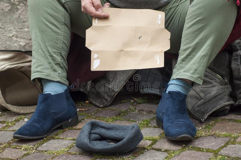 uomo senza tetto della donna che elemosina con il cartone nella via fotografia stock
