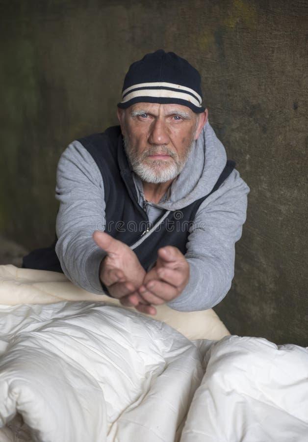 Uomo senza tetto maturo che sembra alimentato su, dando le sue mani immagini stock