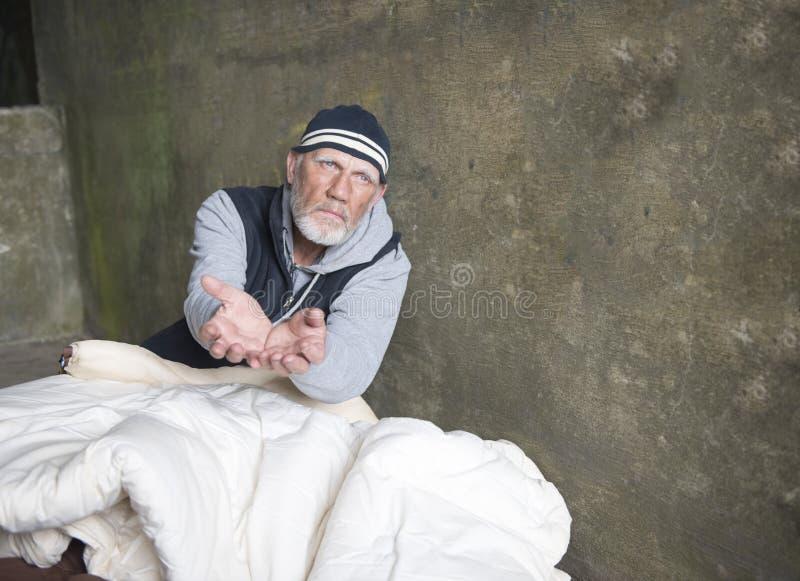 Uomo senza tetto maturo che sembra alimentato su, dando le sue mani fotografie stock libere da diritti