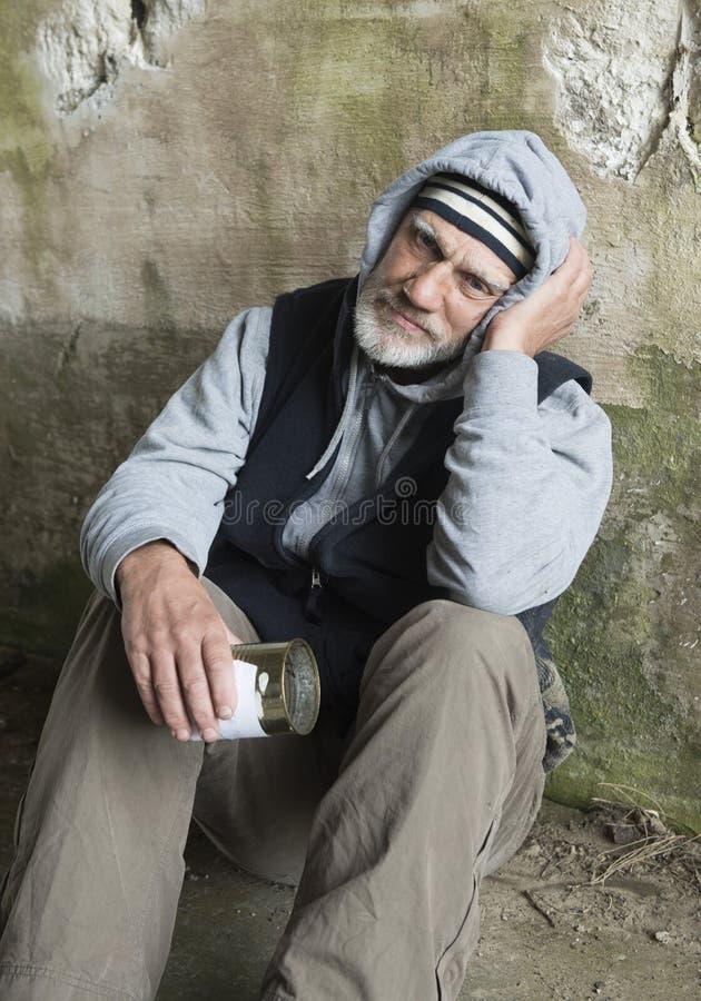 Uomo senza tetto maturo che sembra alimentato su, tenendo un barattolo di latta vuoto fotografia stock libera da diritti