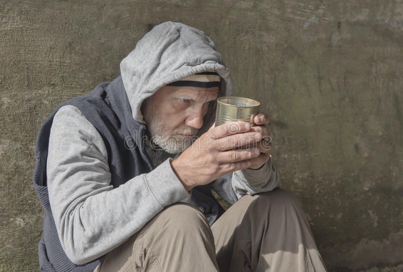 Uomo senza tetto maturo che sembra alimentato su, tenendo un barattolo di latta vuoto immagine stock