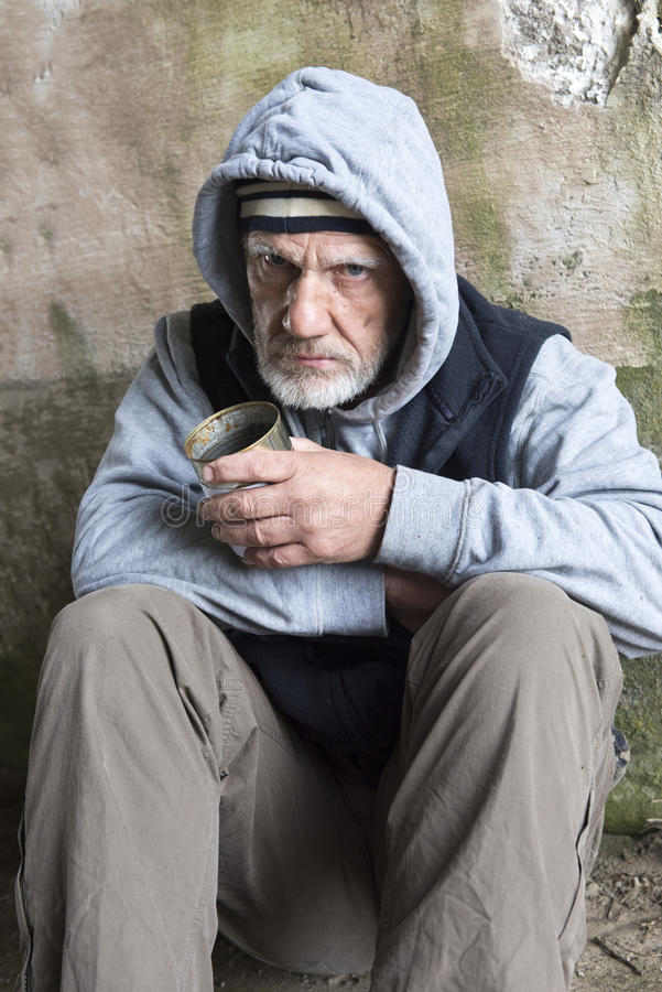 Uomo senza tetto maturo che sembra alimentato su, tenendo un barattolo di latta vuoto fotografie stock libere da diritti