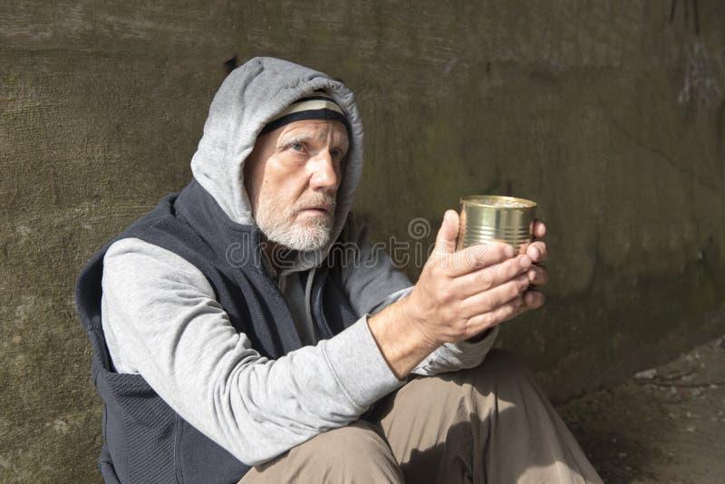 Uomo senza tetto maturo che sembra alimentato su, tenendo un barattolo di latta vuoto fotografie stock