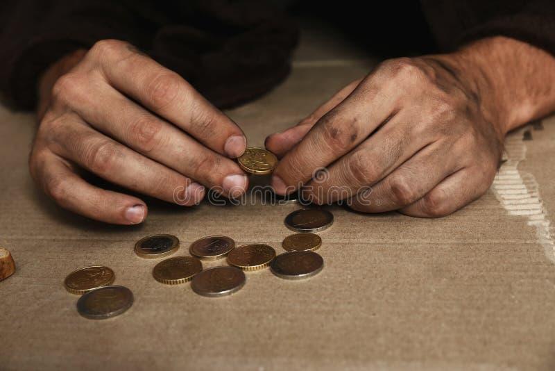 Uomo senza tetto povero che conta le monete sul pavimento fotografia stock