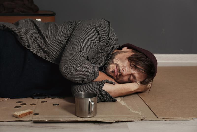 Uomo senza tetto povero che dorme sul pavimento immagine stock