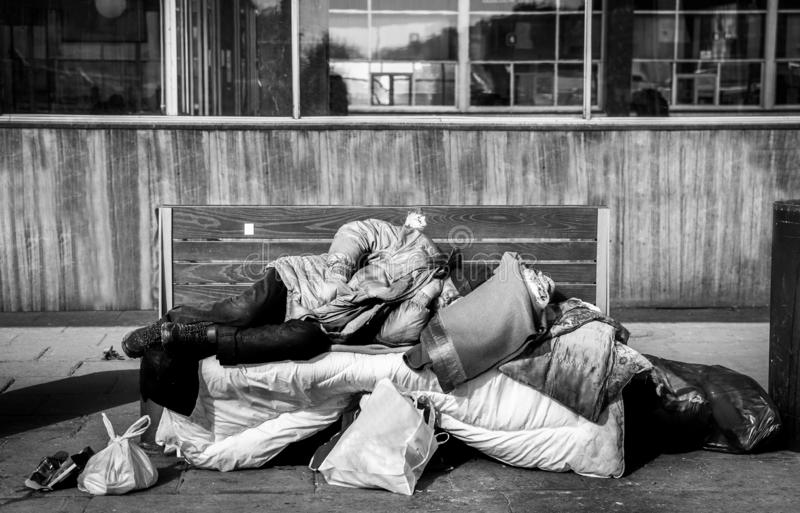 Uomo senza tetto, uomo senza tetto povero o rifugiato che dorme sul banco di legno sulla via urbana nella città con le borse dei  fotografia stock libera da diritti