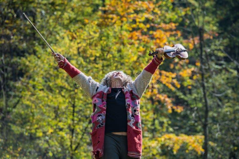 Uomo senza tetto senior con il vecchio maglione lacerato che celebra vita fotografie stock