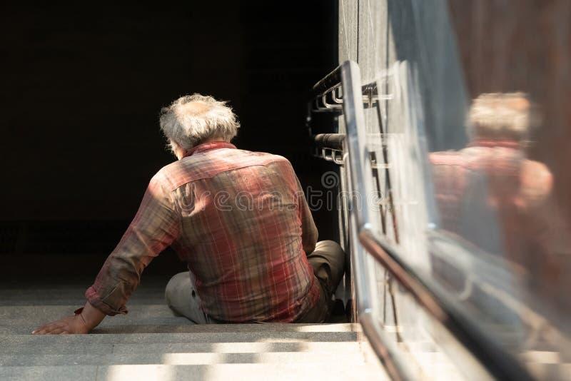 Uomo senza tetto sulla via del passaggio pedonale, concetto senza tetto immagini stock