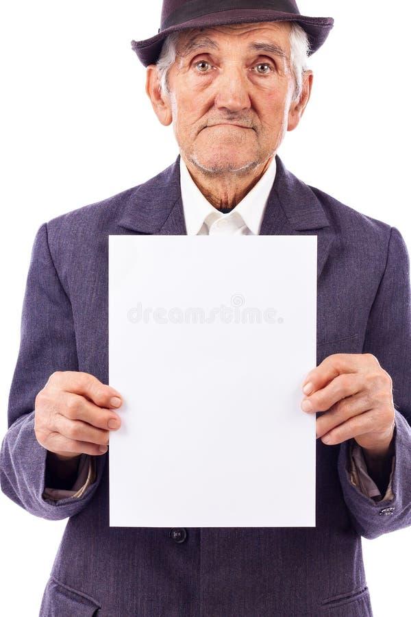 Uomo serio anziano che tiene un foglio di carta bianco vuoto fotografia stock