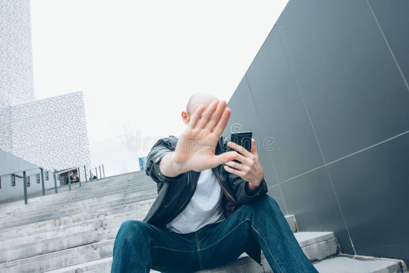 Uomo serio barbuto calvo adulto con seduta mobile nella macchina fotografica di chiusura della scala a mano, non più foto immagini stock libere da diritti