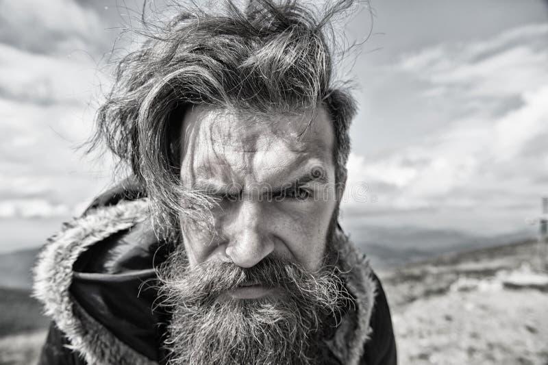 Uomo serio bello barbuto sulla cima della montagna immagine stock