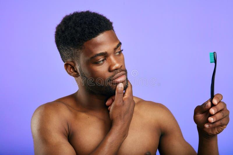 Uomo serio che controlla il suo spazzolino da denti fotografie stock libere da diritti