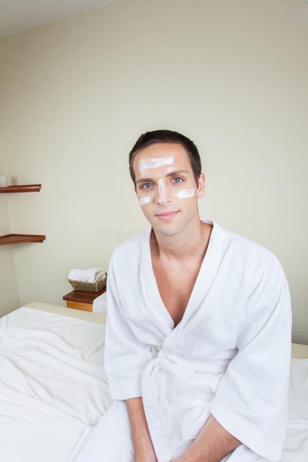 Uomo serio che si siede con la crema sul suo fronte immagini stock libere da diritti