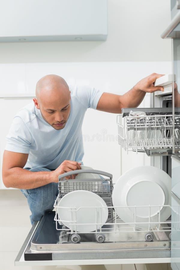 Uomo serio che utilizza lavastoviglie nella cucina immagine stock libera da diritti