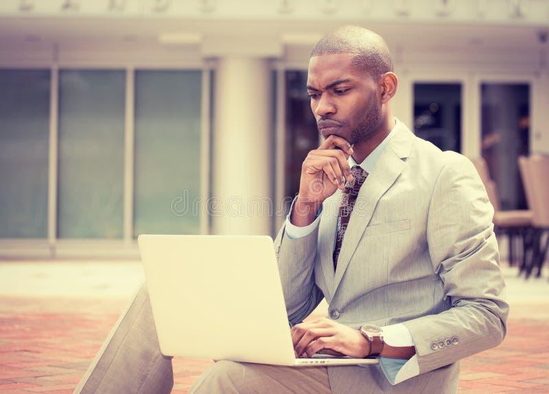 Uomo serio di affari che lavora al computer portatile immagine stock