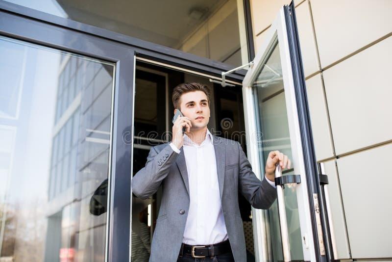 Uomo serio di affari in vestito che parla sul telefono in ufficio e che tiene la porta immagini stock libere da diritti