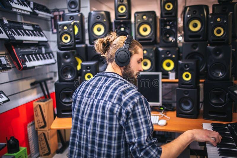 Uomo serio e concentrato del oyung che crea musica in studio Registra la musica giocando sulla tastiera Lavoro dei pantaloni a vi immagini stock