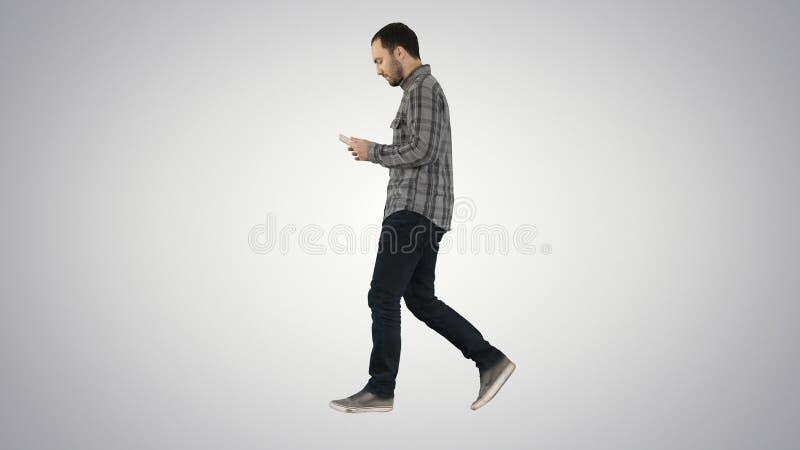 Uomo serio sicuro che cammina e che lavora in compressa sul fondo di pendenza fotografia stock