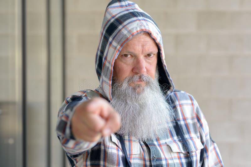 Uomo severo che indossa indicare della cima incappucciata fotografie stock