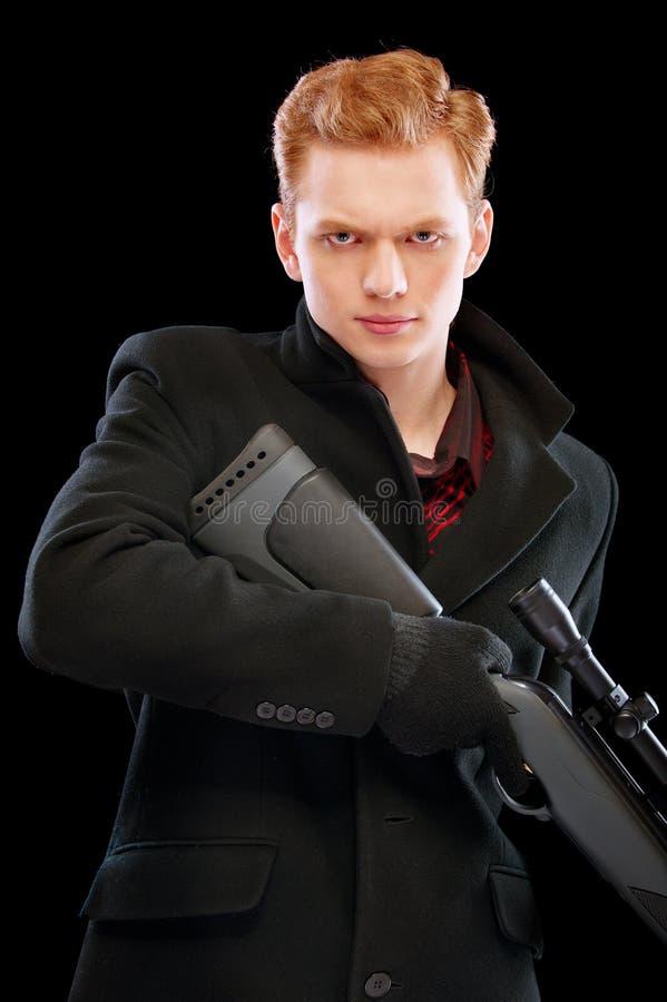 Uomo severo con il fucile del tiratore franco in mani fotografie stock