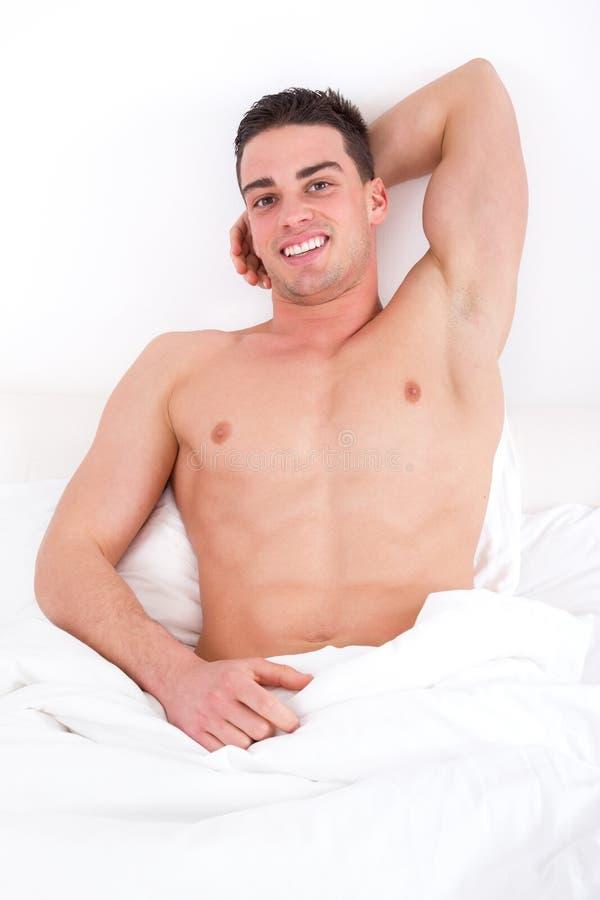 Uomo sexy che si trova sul sorridere del letto fotografia stock