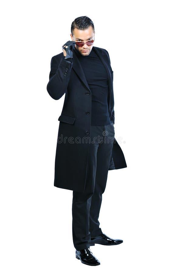Uomo sexy in cappotto nero isolato su bianco immagini stock
