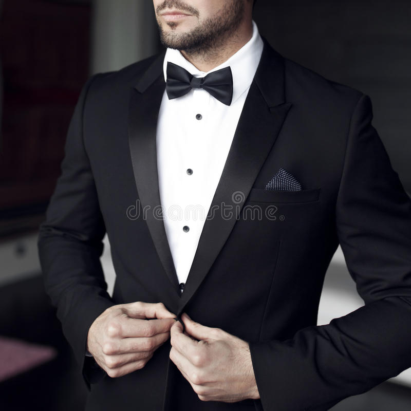 Uomo sexy in smoking e farfallino fotografia stock