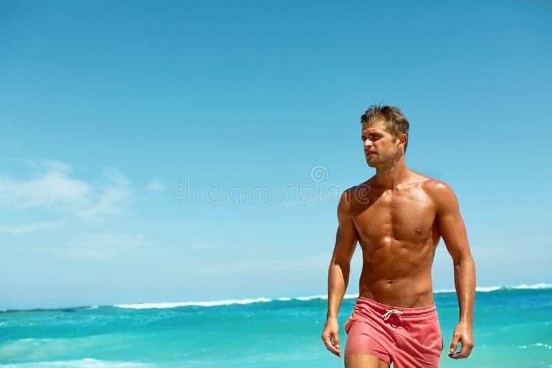 Uomo sexy sulla spiaggia di estate Maschio che si rilassa vicino al mare immagini stock