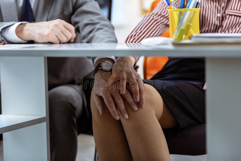 Uomo sfacciato che tormenta il suo collega espressivo mentre toccando le gambe nude fotografia stock libera da diritti