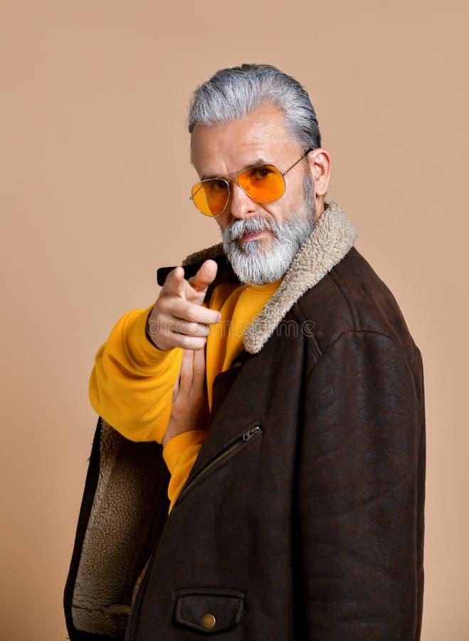 Uomo sicuro con una barba ed i baffi in un cappotto di cuoio, uno sguardo severo alla macchina fotografica ed indicare su voi immagini stock libere da diritti