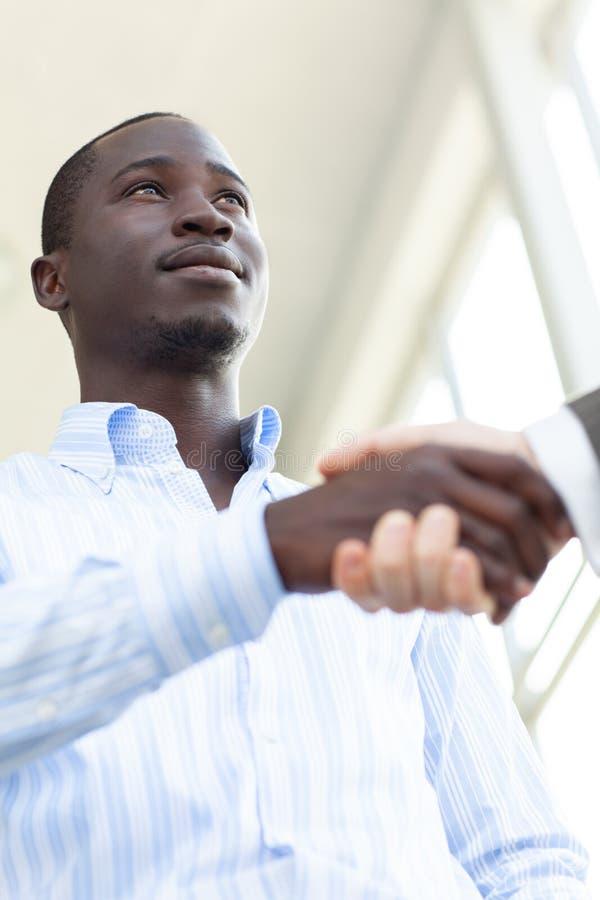 Uomo sicuro di affari due che stringe le mani nel corso di una riunione nell'ufficio, nel successo, trattare, accogliere e nel co immagine stock
