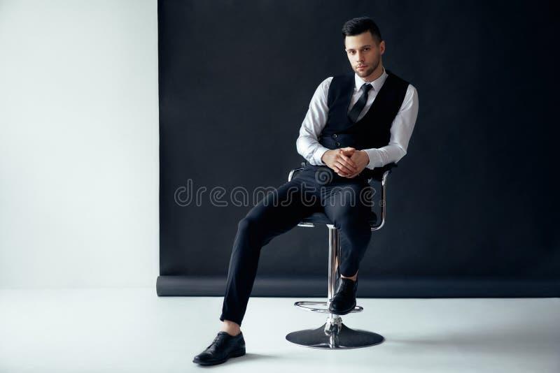 Uomo sicuro elegante che posa e che si siede sulla sedia su fondo in bianco e nero immagini stock libere da diritti