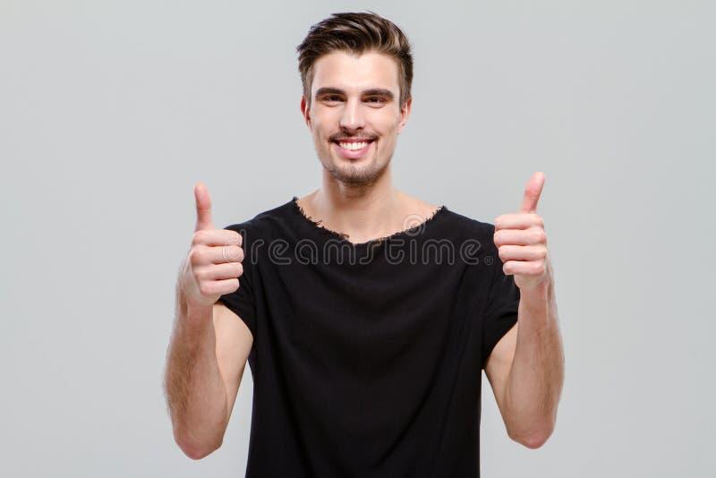 Uomo sicuro felice che mostra i pollici su immagini stock