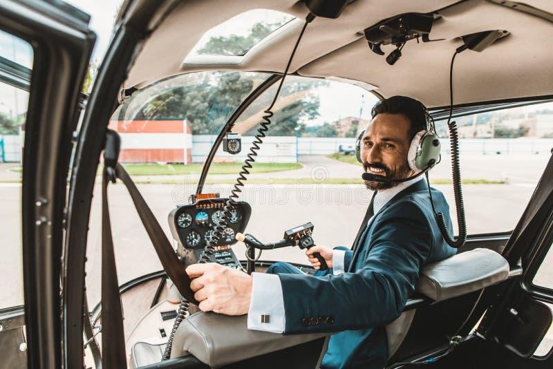 Uomo sicuro in vestito elegante che sorride mentre essendo nella cabina dell'elicottero fotografia stock libera da diritti