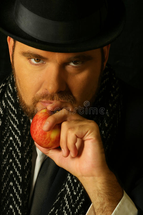 Uomo sinistro con la mela fotografie stock