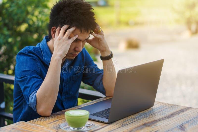 Uomo sollecitato che per mezzo del computer portatile immagini stock