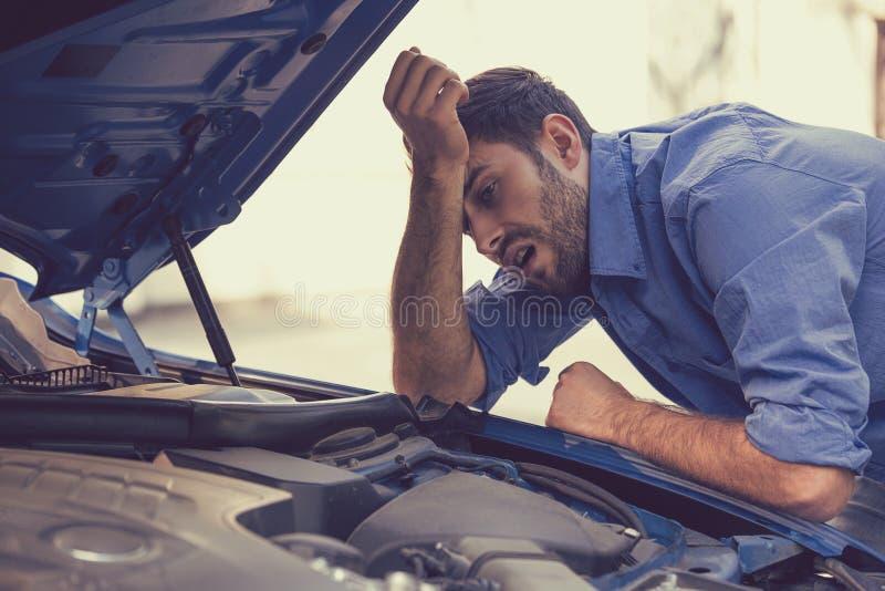 Uomo sollecitato con l'automobile rotta che esamina motore guastato fotografie stock libere da diritti