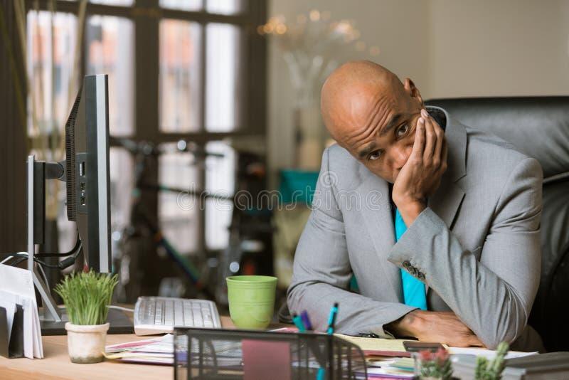 Uomo sollecitato o stanco nel suo ufficio fotografie stock